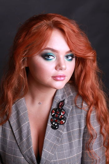 Close-up portrait of sensuous young woman against black background