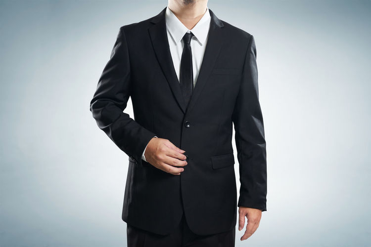 Midsection of businessman wearing suit against gray background