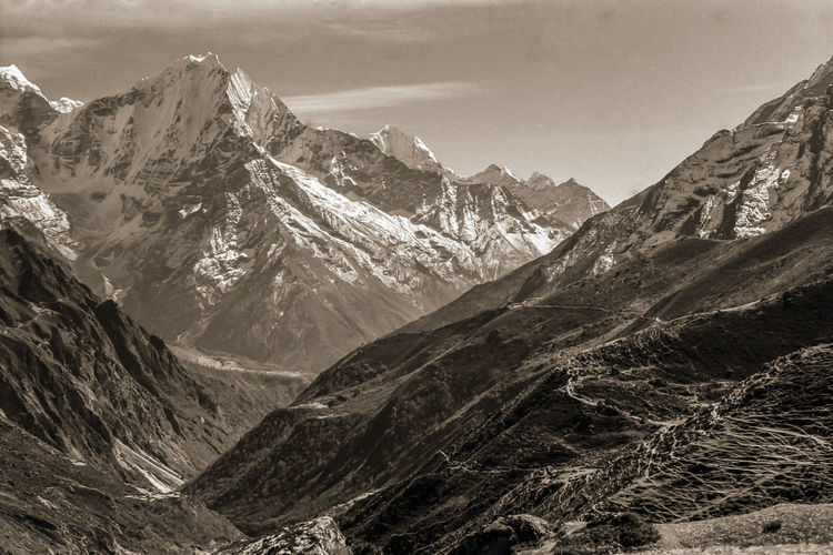 Colossal snowy mountains and deep valleys amid the himalayas, in nepal. black and white photo.