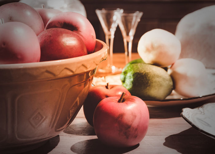 A bowl of English eating apples in a rustic kitchen Food And Drink Healthy Eating Food Fruit Wellbeing Freshness Still Life Table Indoors  No People Container Close-up Red Apple - Fruit Bowl Tomato Focus On Foreground Wood - Material Pear Vegetable Ripe Apple Apples Rustic Rustic Kitchen