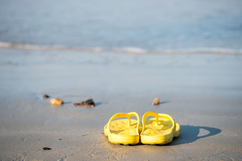 Close-up of yellow shoes on beach