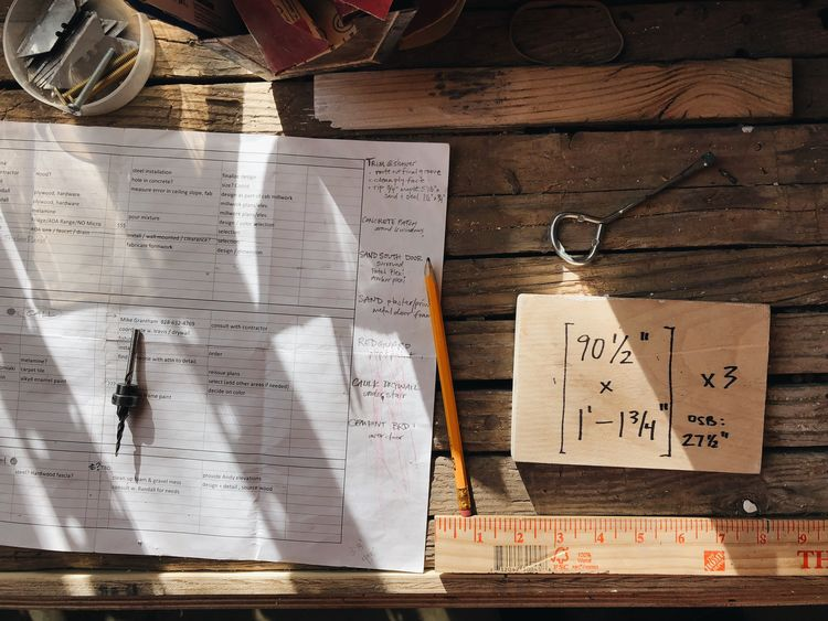 Sunlight and shadows over a construction work bench Tools Of The Trade Tools Workshop Work In Progress Construction Text Communication No People Paper Handwriting  Western Script Indoors  Directly Above Wood - Material Still Life Document Close-up Day