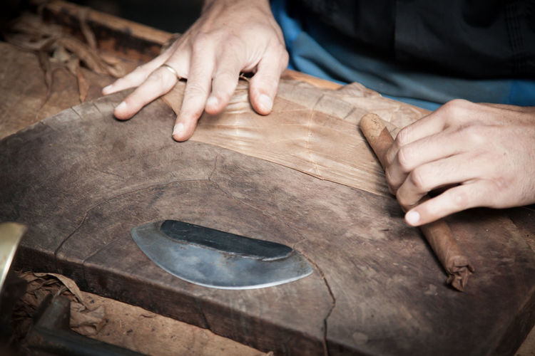 Midsection Of Worker Making Cigar