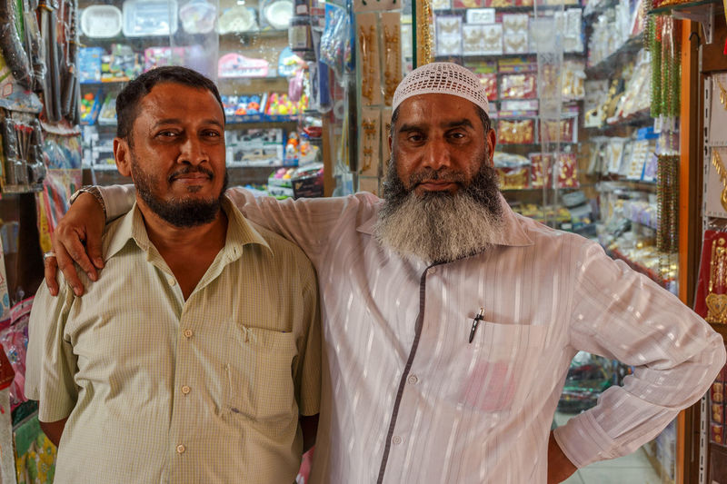 Two businessmen on the Deiro Souk Portrait Two People Looking At Camera Waist Up Front View Standing Adult Men Mid Adult People Clothing Store Facial Hair Beard Mid Adult Men Shopping Mature Adult Males  Couple - Relationship Consumerism Souk Dubai Deira Bearded