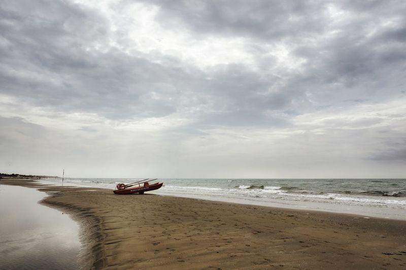 Lifeboat on sandbar against cloudy sky