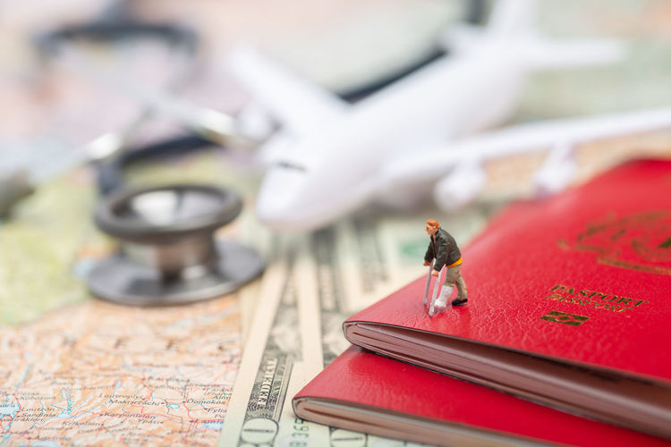 Miniature man injured in foreign land concept. Aeroplane Castle Country Foreign Holiday Leg Passport Tourist US Dollar Accident Aircraft Airplane Broken Close-up Crutches Disability  Figurine  Injury Insurance Medical Miniature Mishap Stethoscope  Toy Vacation