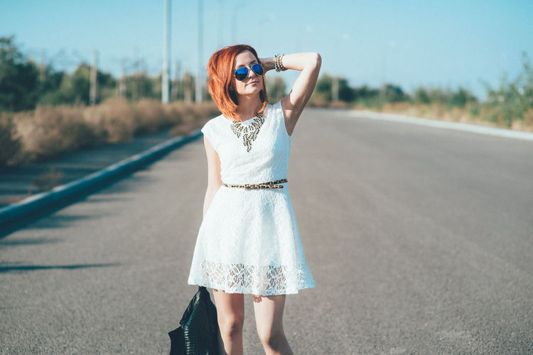 Woman wearing sunglasses standing on road