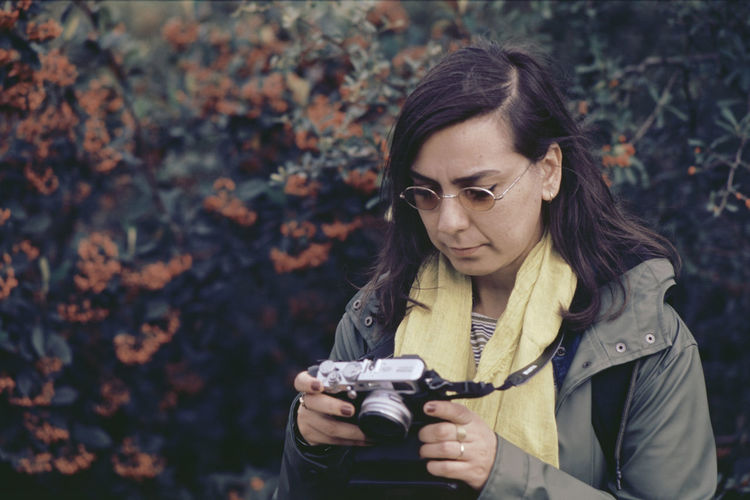 Close-up of woman holding camera against trees in forest