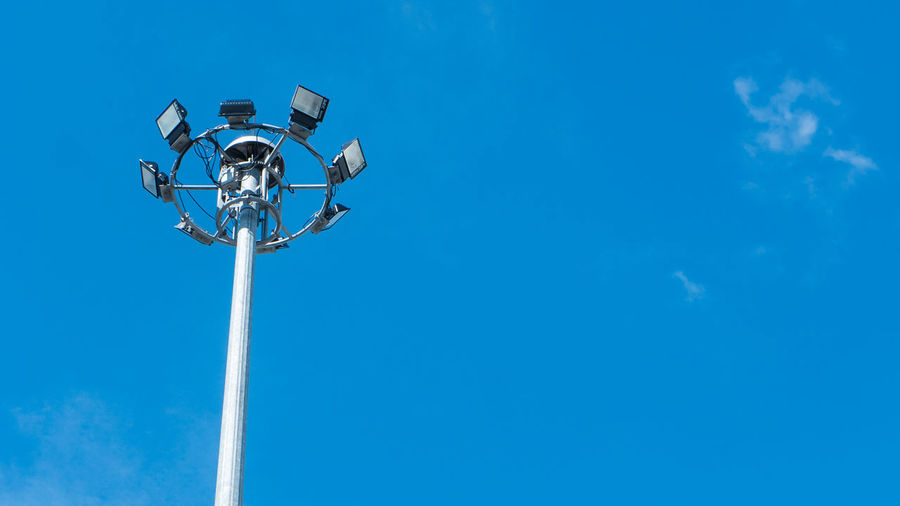 Low angle view of floodlights against clear blue sky