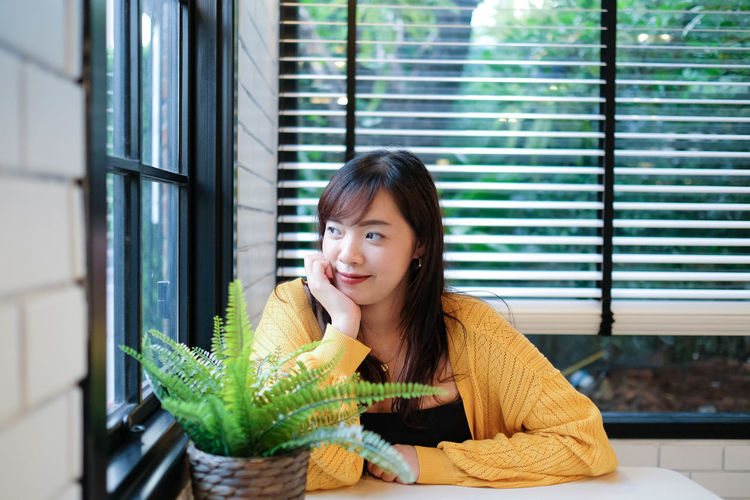 Close up of young pretty asian woman sitting in the cafe feeling relax.
