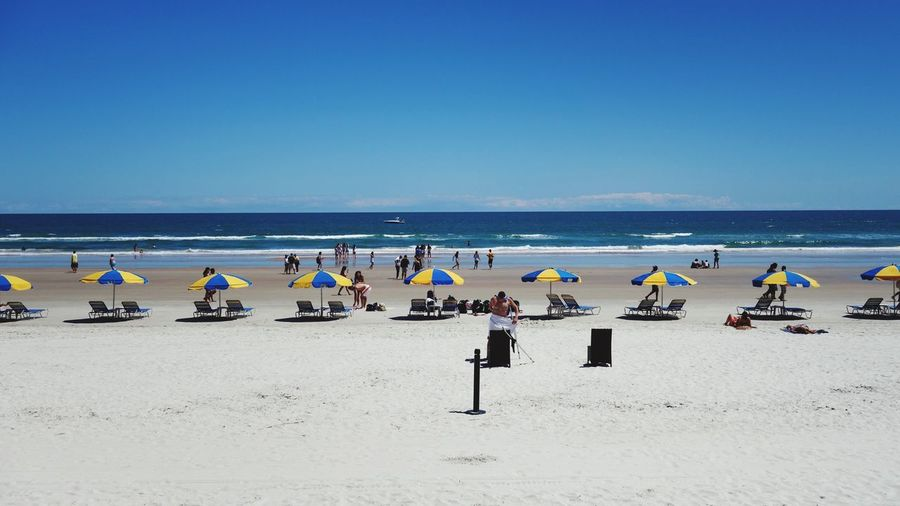 Beach Umbrellas In A Row Ocean View Water Blue Sky Midday Daytime People Sea Horizon Over Water Blue Clear Sky Sand Sunlight Outdoors Scenics Tranquility Nature Sky