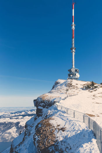 The Rigi is a mountain massif of the Alps, located in Central whole massif is almost entirely surrounded by the water of three different water bodies: Lake Lucerne, Lake Zug and Lake Lauerz. Radio Antenna - Aerial Architecture Blue Blue Sky Built Structure Clear Sky Cold Temperature Communication Covering Day Global Communications Mountain Mountain Peak Nature No People Outdoors Satellite Sky Snow Snowcapped Mountain Spire  Sunlight Tall - High Technology Tower Winter