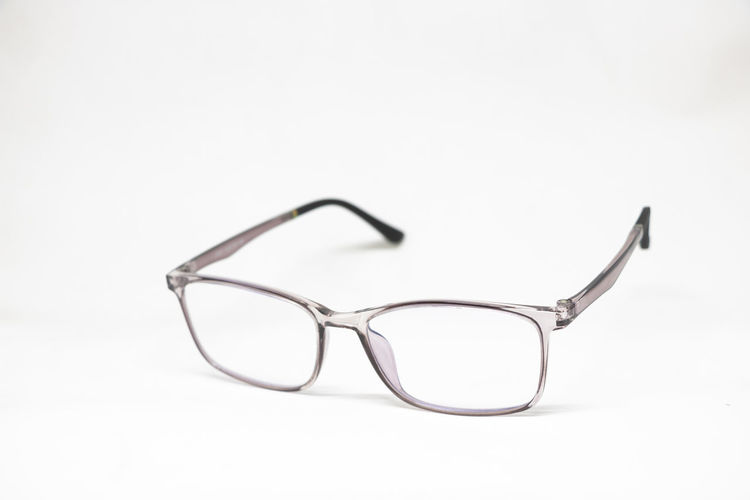 Close-up of eyeglasses on table against white background
