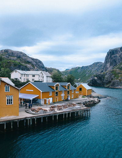 Mountain Architecture Built Structure Mountain Range Building Exterior Day Nature Outdoors Norway Houses Fisherhouse Ocean Fjord Water Sky Building Cloud - Sky Waterfront House Beauty In Nature Sea Scenics - Nature Nautical Vessel Residential District Tourist Resort No People Turquoise Colored