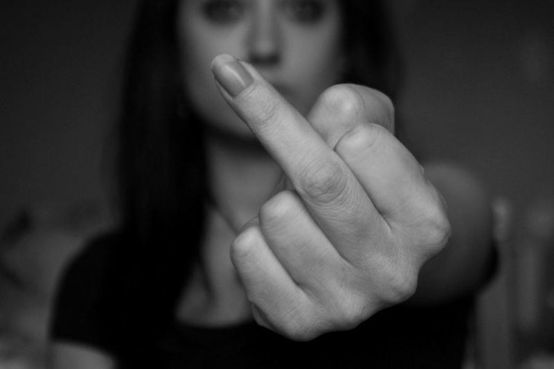 Close-up of woman showing middle finger