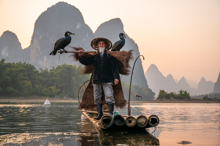 Portrait of man wearing hat standing on raft against mountain and sky