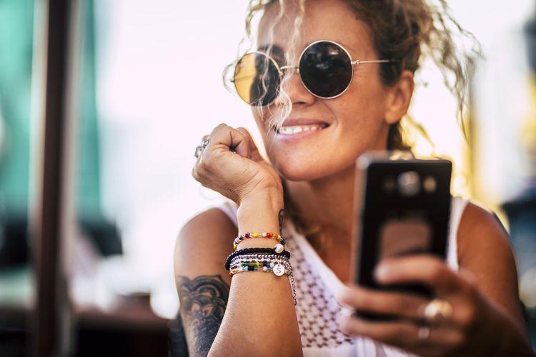 Smiling woman using mobile phone