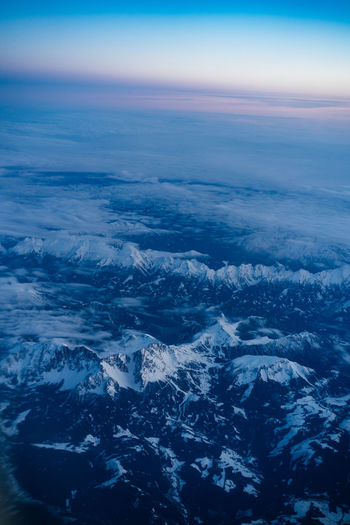 Aerial view of sea and snowcapped mountain against sky