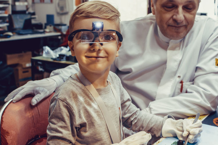 Little boy working on school science project with his teacher in engineering laboratory.