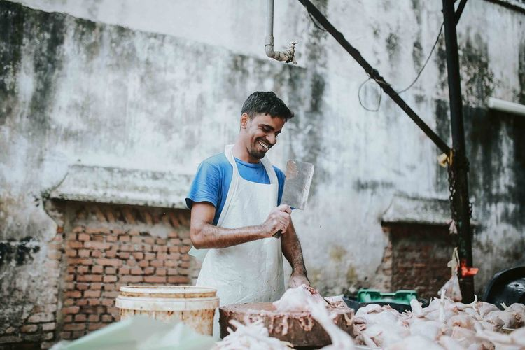 Happy butcher cutting meat at market stall