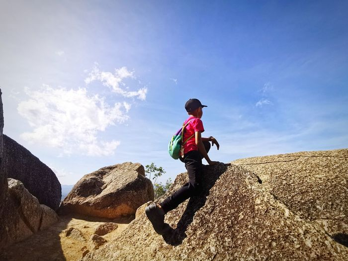 Rear view of boy on rock against sky