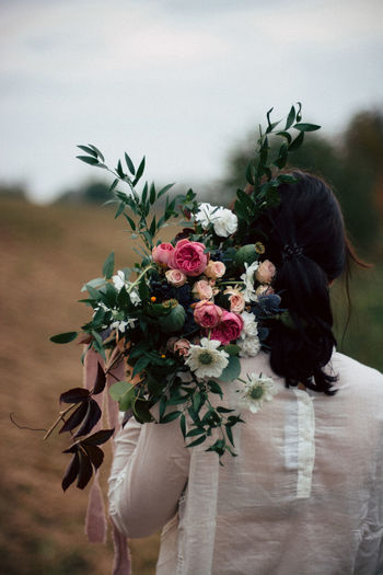 Rear View Of Woman Holding Flower Bouquet