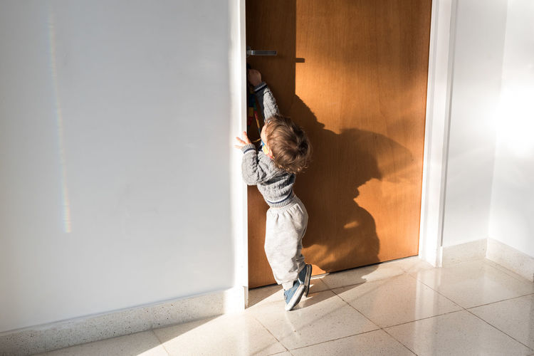 Boy opening door while standing in corridor