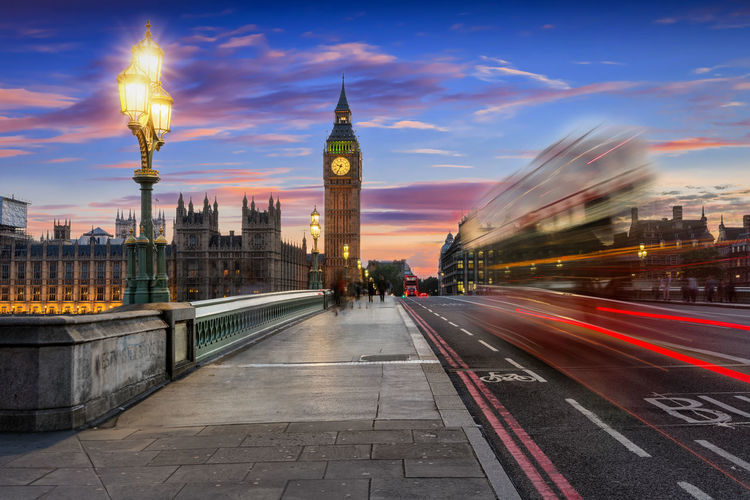 Light trails on westminster bridge with big ben in background during sunset