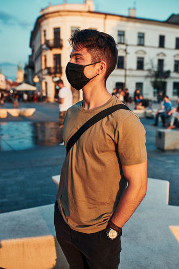 Young man wearing mask standing in city