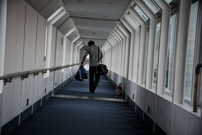 Rear view of man walking in corridor. end of the trip.