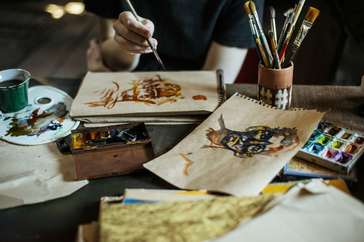 Art And Craft Brush Paintbrush Creativity Craft Indoors  Paint Selective Focus Artist One Person Palette Real People Table Human Hand Occupation Studio Workshop Watercolor Paints Skill  Art And Craft Equipment Hand Holding