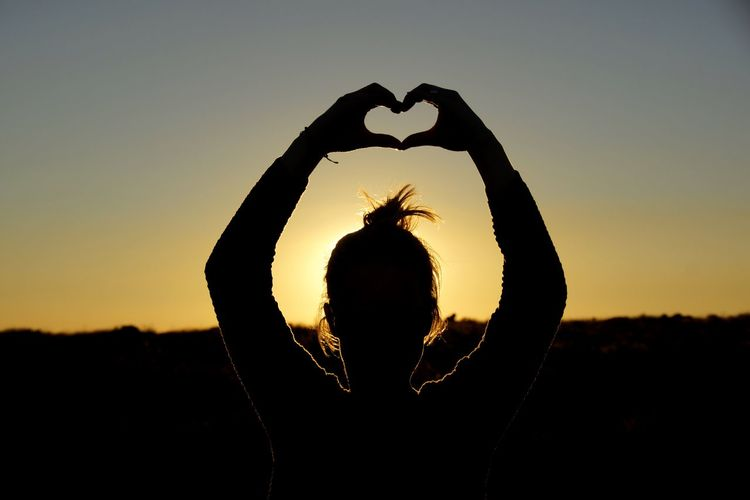 Silhouette woman showing heart shape against sky during sunset