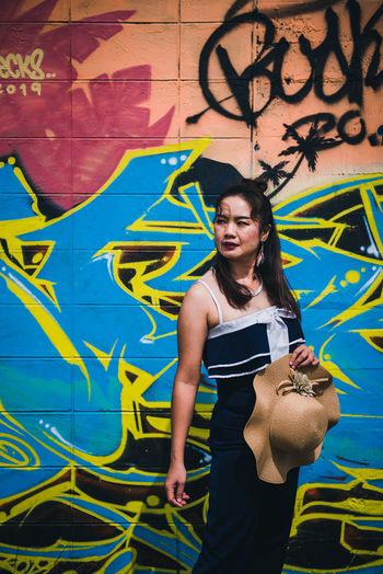 Full length of smiling woman standing against graffiti wall