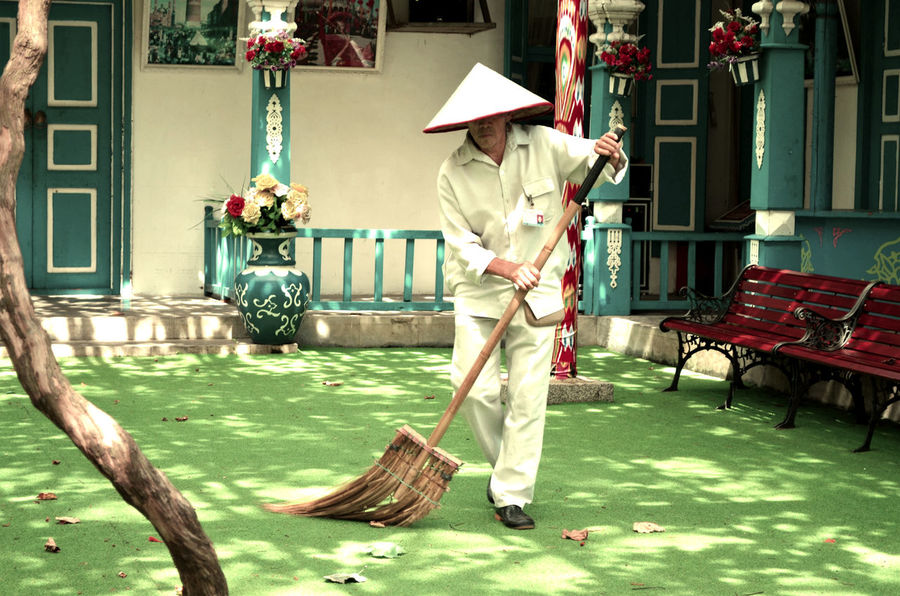 Sweeping the leaves 2 Bamboo Broom Broom Chinese Chinese Hat Conical Hat Day Man Outdoors Sweeping Traditional Traditional House Wiping People And Places Snap a Stranger The City Light