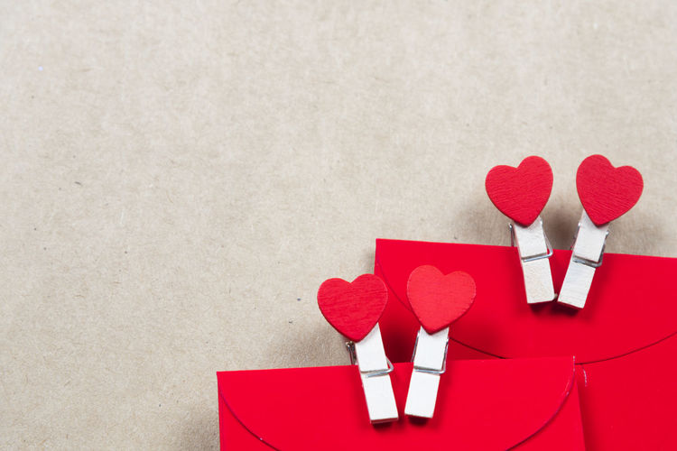Close-up of heart shape with red envelopes on beige background