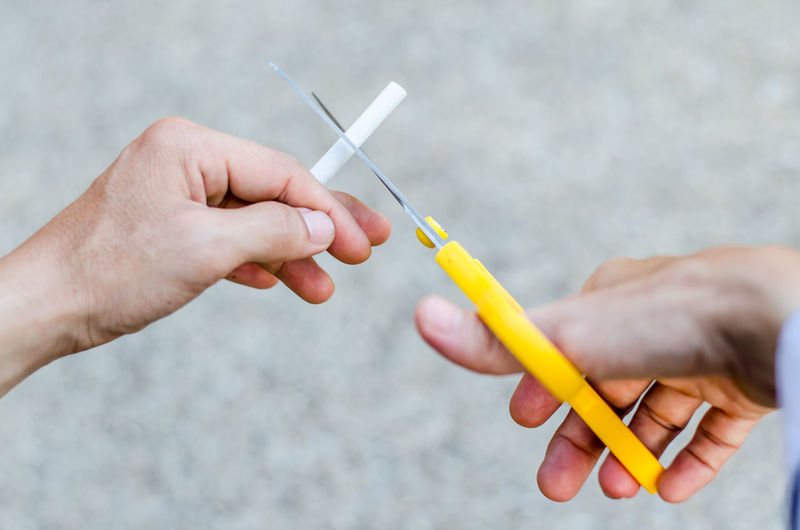 Cropped hands of man cutting cigarette with scissors