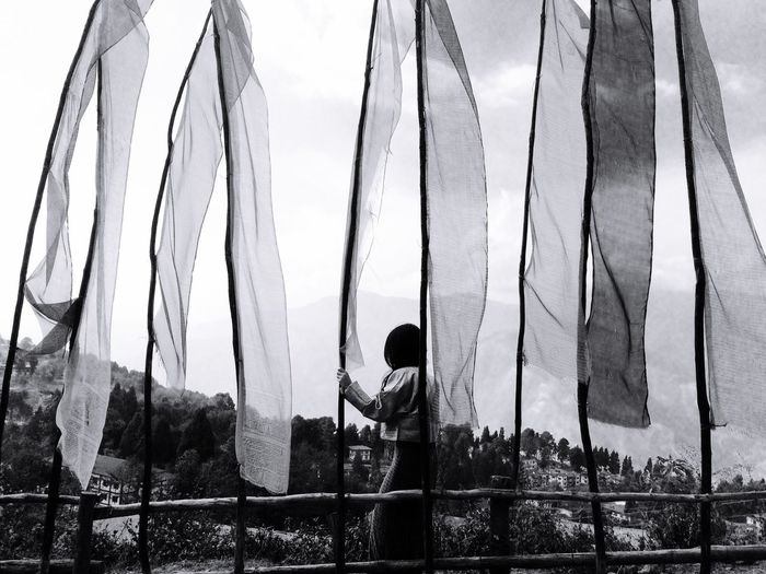 Woman Standing By Prayer Flags Against Sky