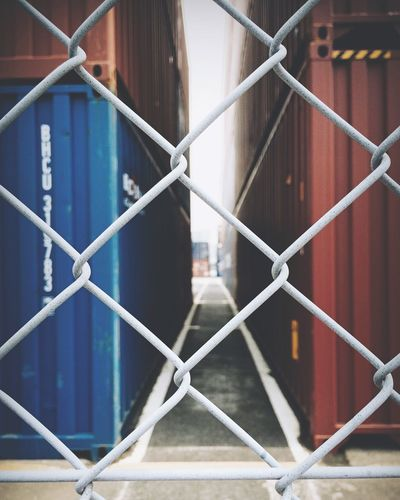 Cargo containers seen through chainlink fence