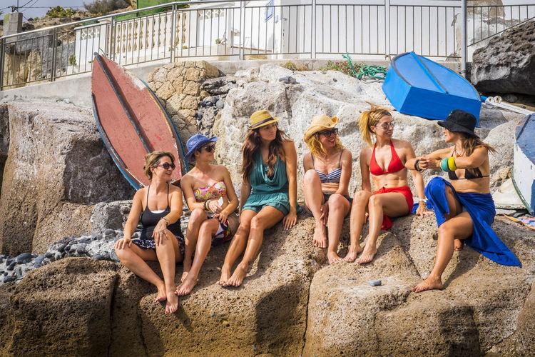 Full length of friends wearing bikini sitting on rock at beach