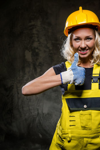 Portrait of smiling female worker showing thumbs up while standing against wall