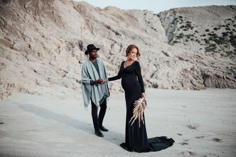Full length of couple standing on sand in desert
