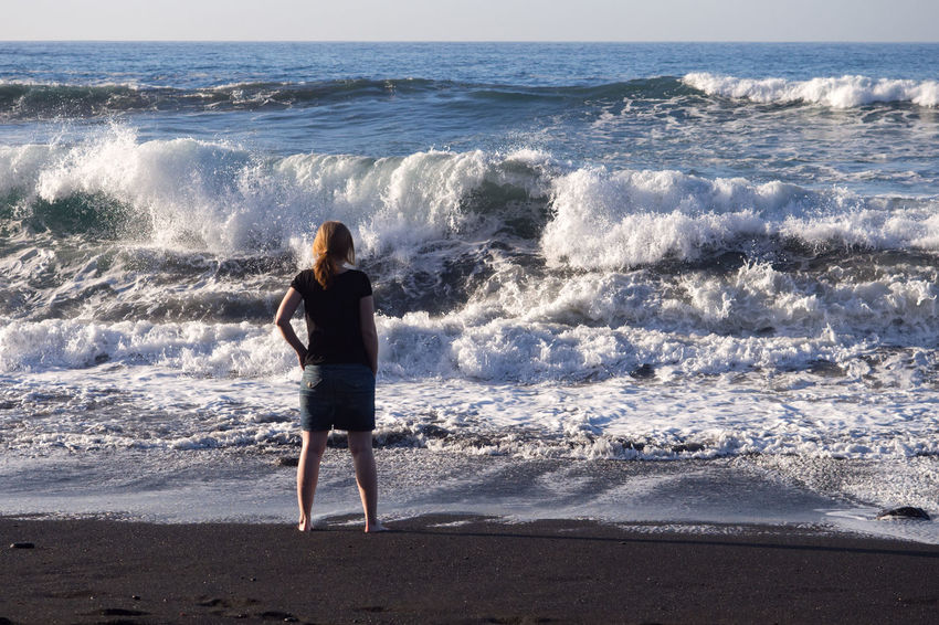 Young woman watching waves at black sand beach on Tenerife island Atlantic Ocean Beach Big Waves Black Sand Breeze Canary Islands Ocean One Person Outdoors Real People Rear View Rough Scenics Sea Shore Storm Stormy Weather Tenerife Water Wave Weather Wind Woman
