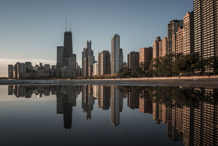 Reflection Of Buildings In Calm Water Against Clear Sky