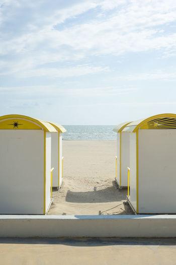 Beach huts at beach against sky