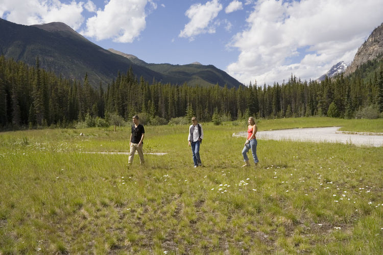 Full Length Of Friends Standing On Grassy Field Against Mountains