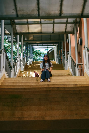 Portrait of young woman sitting on staircase while holding sunglasses at building
