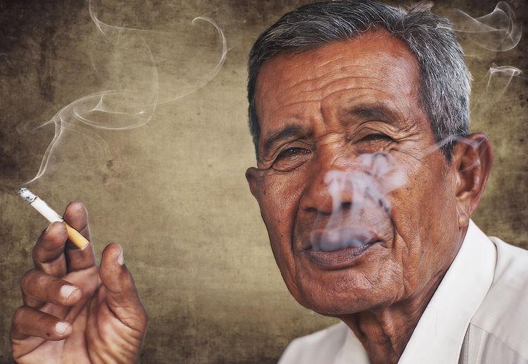 Close-Up Portrait Of Senior Man Smoking Cigarette