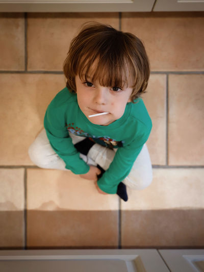Child Childhood One Person Real People Innocence Full Length Lifestyles Boys Indoors  Casual Clothing Cute Males  Men Front View Flooring Tiled Floor Sitting Sweets Eating Lollipop High Angle View