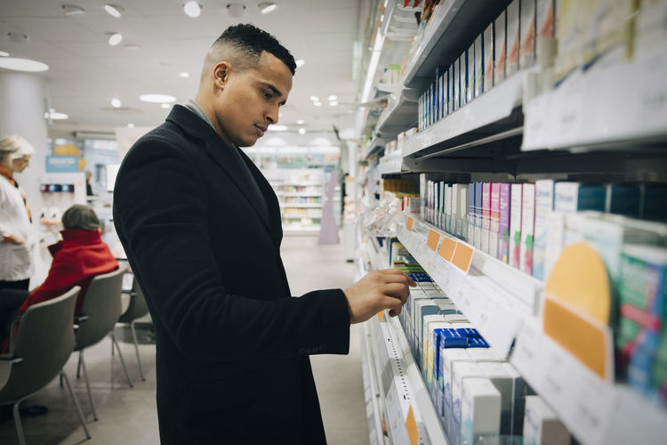 Side view of young man looking at book
