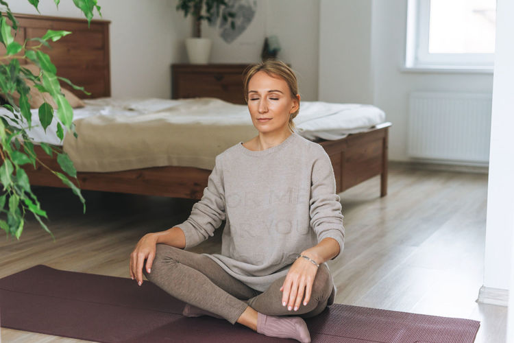 Beautiful blonde young woman in comfortable sport wear practice yoga in cozy bedroom at the home
